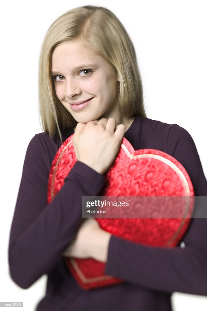 beauty portrait of a young adult female as she closely hugs a valentines heart box of chocolates : Foto de stock