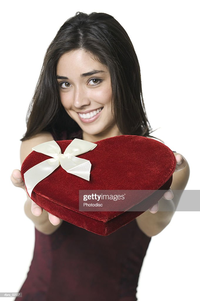 beauty portrait of a young adult female as she holds out a valentines heart box of chocolates : Foto de stock
