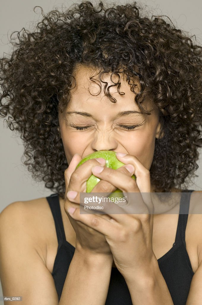beauty portrait of a young adult female in a black tank top as she bites into an apple : Foto de stock