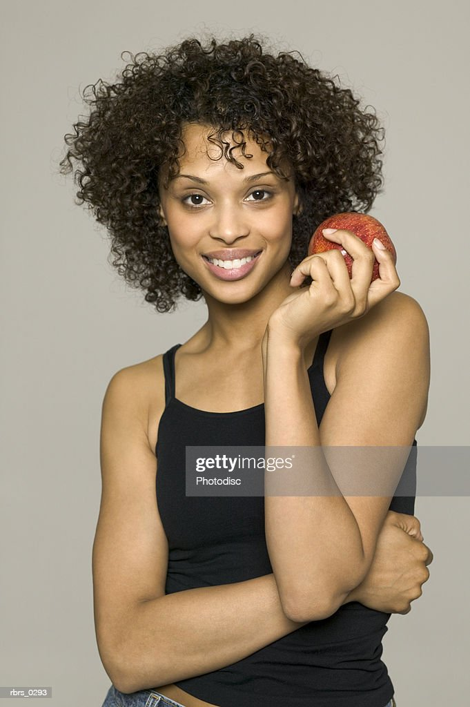beauty portrait of a young adult female in a black tank top as she holds up an apple : Foto de stock