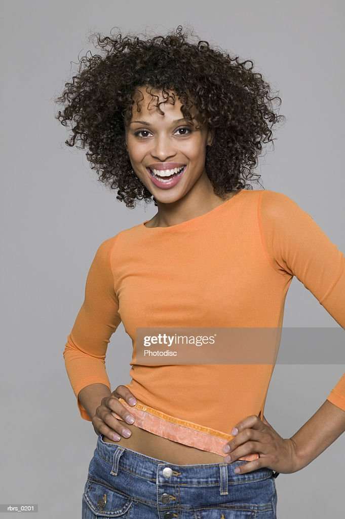 beauty portrait of a young adult female in an orange shirt as she smiles brightly : Foto de stock