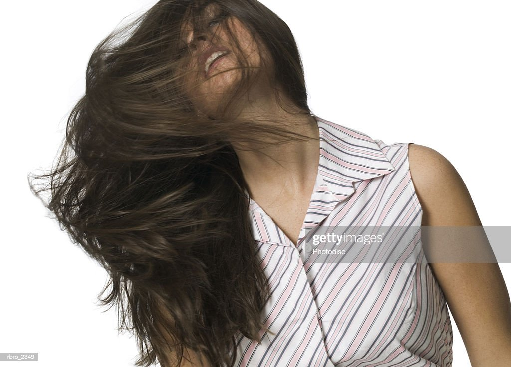beauty portrait of a young adult woman in a stripped dress as she tosses her hair around : Foto de stock