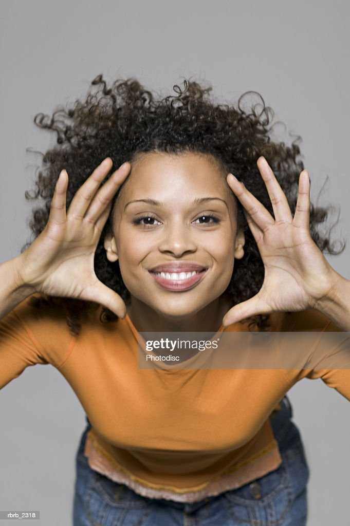 beauty portrait of a young adult woman in an orange shirt as she playfully gestures and smiles : Foto de stock