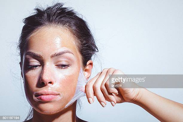 Beauty portrait of a young woman applying-removing face mask