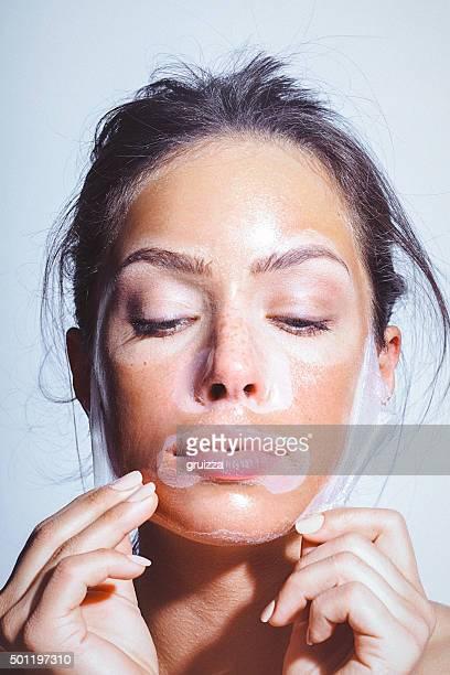Schönheit Porträt einer jungen Frau mit Maske im Gesicht anwenden entfernen