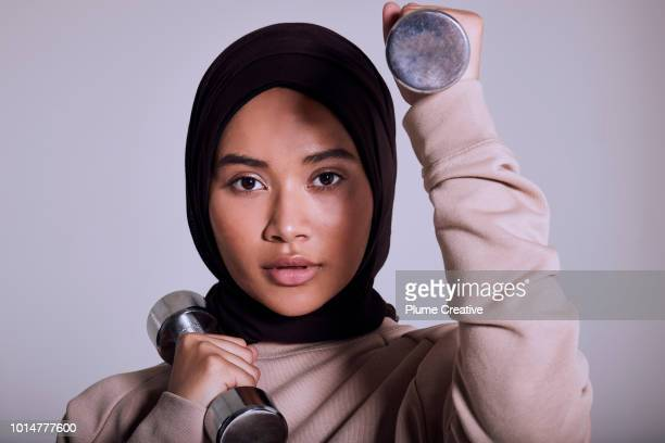 Beauty portrait of Muslim woman with hand weights