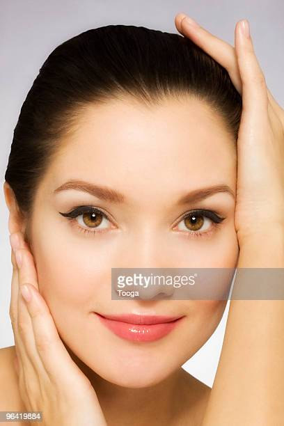 Beauty portrait of woman with hands holding face