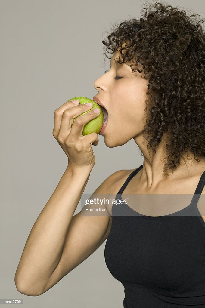 beauty portrait of young adult female in a black tank top as she bites into a green apple : Foto de stock