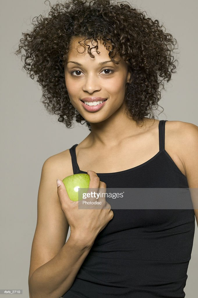 beauty portrait of young adult female in a black tank top as she holds a green apple : Foto de stock