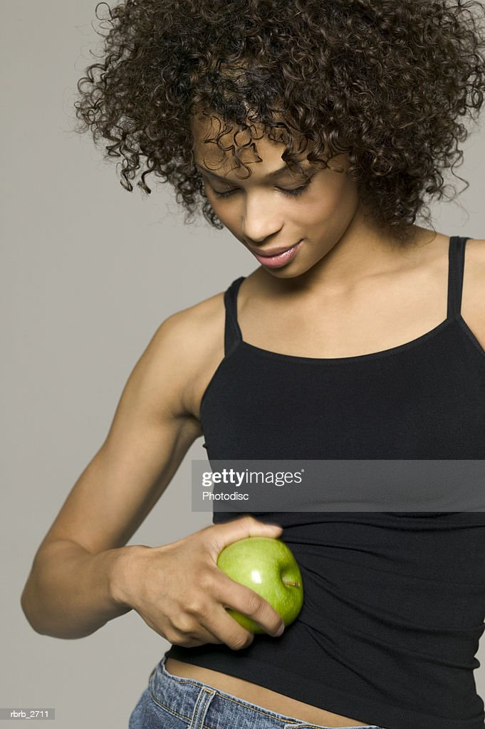 beauty portrait of young adult female in a black tank top as she cleans a green apple : Foto de stock