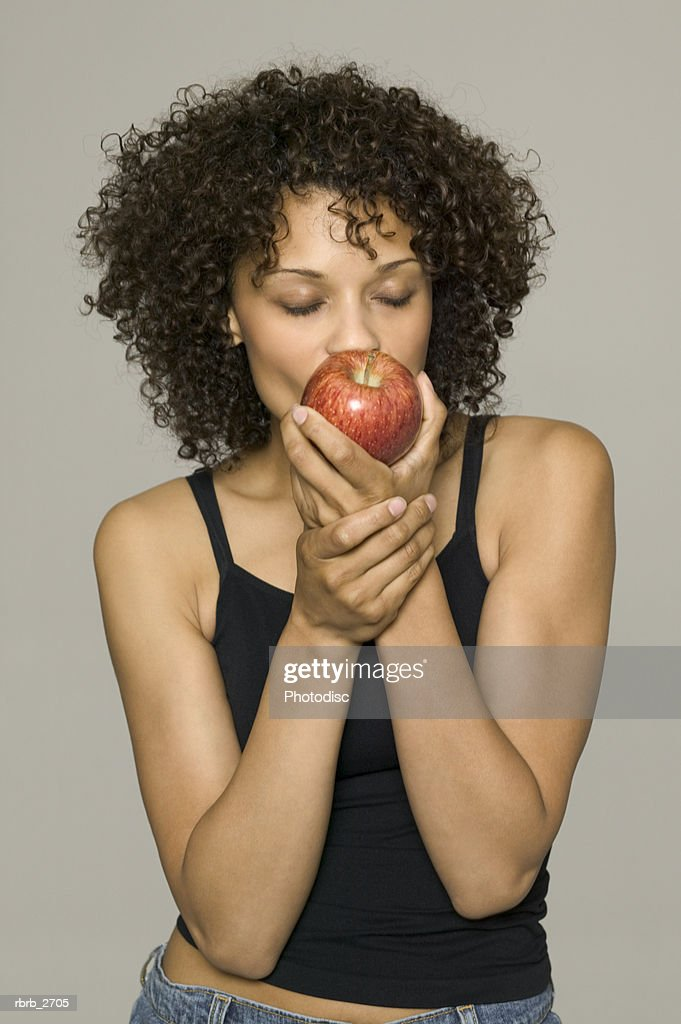 beauty portrait of young adult female in a black tank top as she bites into an apple : Foto de stock