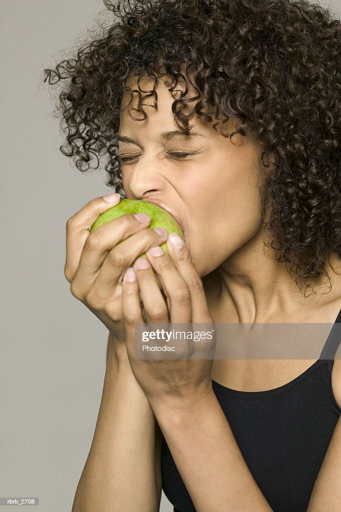 beauty portrait of young adult female in a black tank top as she eats an apple : Foto de stock
