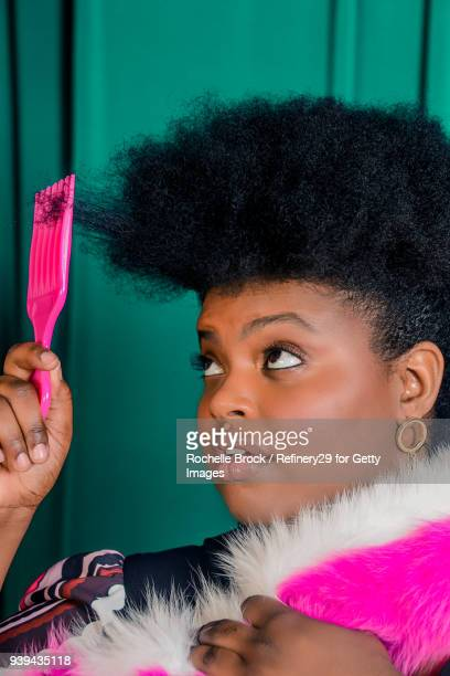 Beauty Portrait of Young Confident Woman with Afro Styling Her Hair with Pick