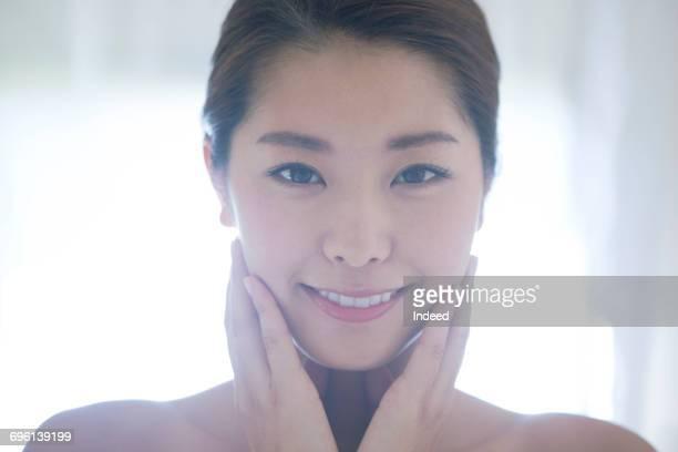 Beauty portrait, young woman touching her cheek