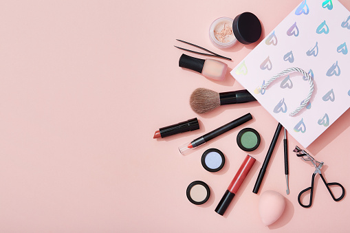 Beauty products and a gift bag flat lay on pink background 909050548