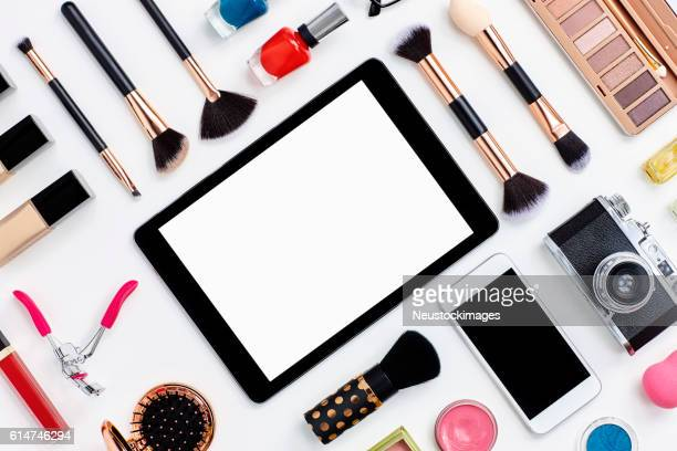 Beauty products surrounding digital tablet on white background