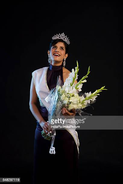 Beauty queen holding a bouquet of flowers
