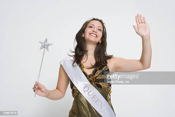 beauty queen waving hand, holding magic wand, smiling - sjerp stockfoto's en -beelden