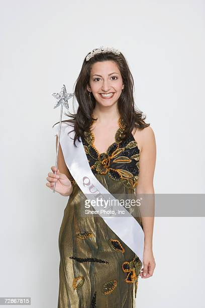 Beauty queen wearing sash, holding magic wand, smiling