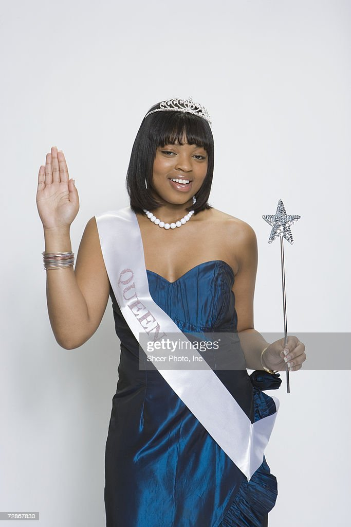 Beauty queen wearing tiara and sash, holding magic wand, portrait : Stock Photo