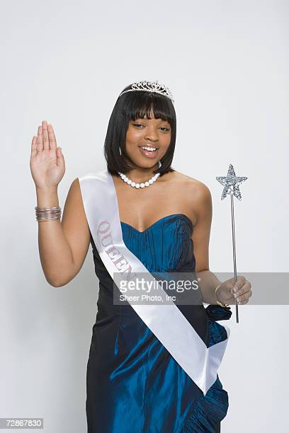 Beauty queen wearing tiara and sash, holding magic wand, portrait