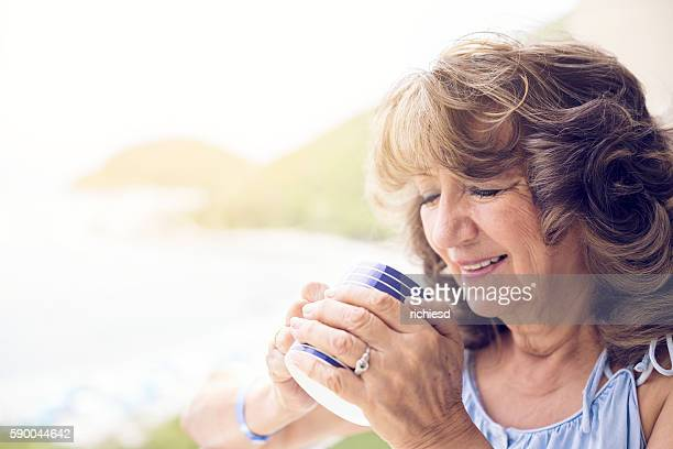 Beauty senior woman drinking a cup of coffee