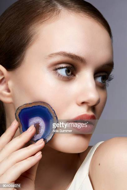 beauty shot of a woman holding a blue gemstone on her cheek