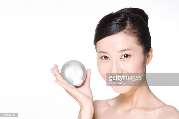Beauty shot of a young woman holding a ball of ice