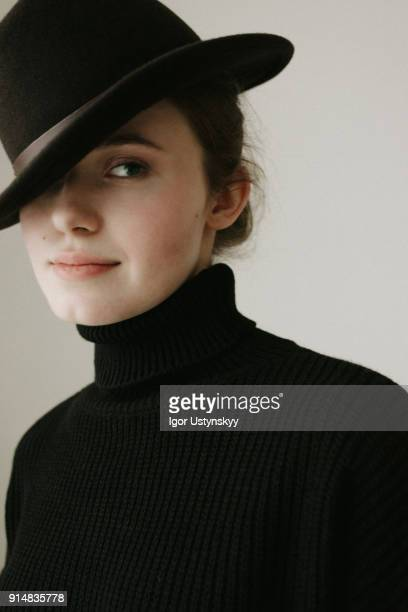 Beauty shot of a young woman wearing a black hat