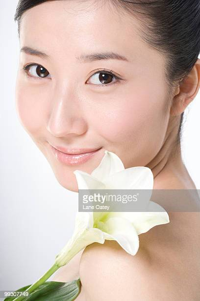 Beauty shot of a young woman with a Lily flower