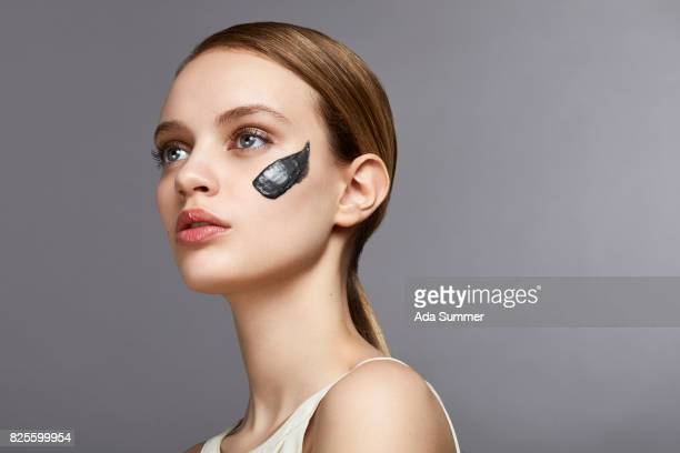 Beauty shot of a young woman with charcoal clay mask spot on her cheek