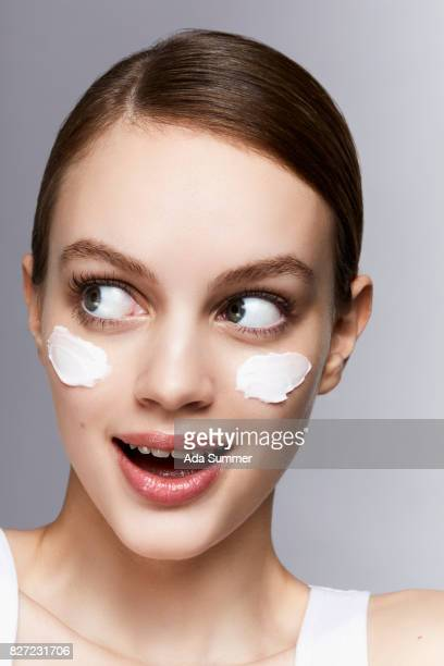 Beauty shot of a young woman withlotion on her cheek