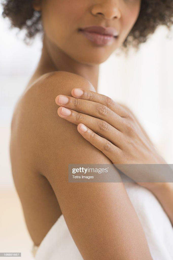 Beauty shot of woman touching shoulder, studio shot : Stock Photo