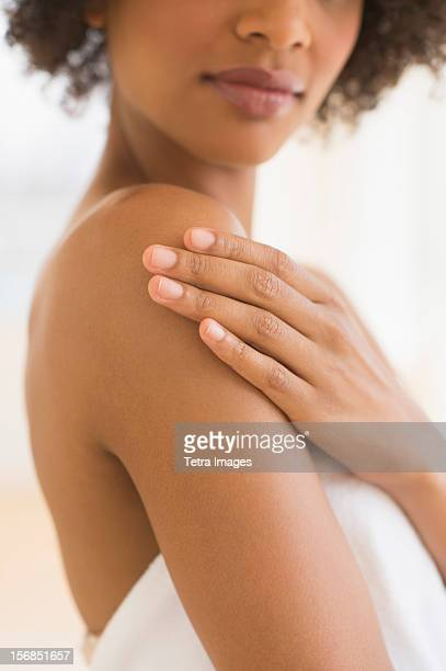 Beauty shot of woman touching shoulder, studio shot