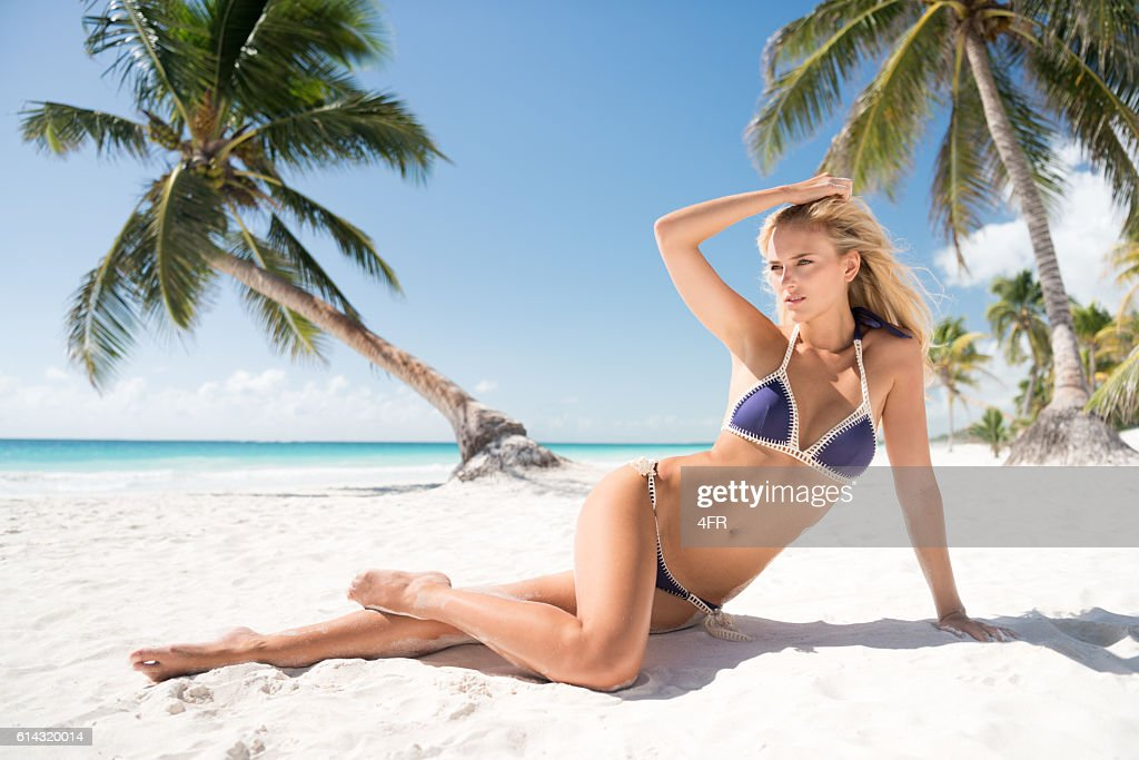 Beauty sitting in front of palm trees by the ocean : Stock Photo