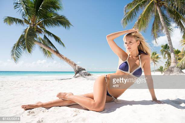 Beauty sitting in front of palm trees by the ocean