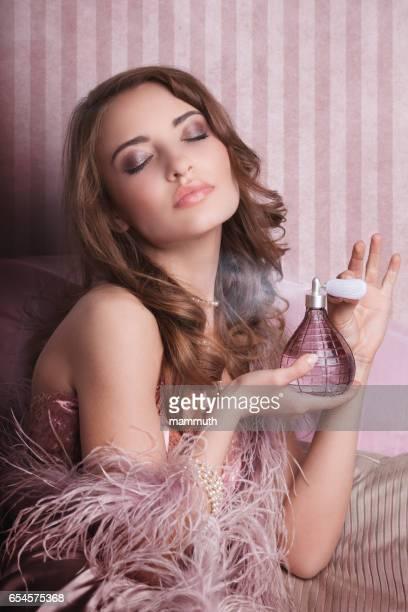 bellezza spruzzando profumo su se stessa - profumato foto e immagini stock