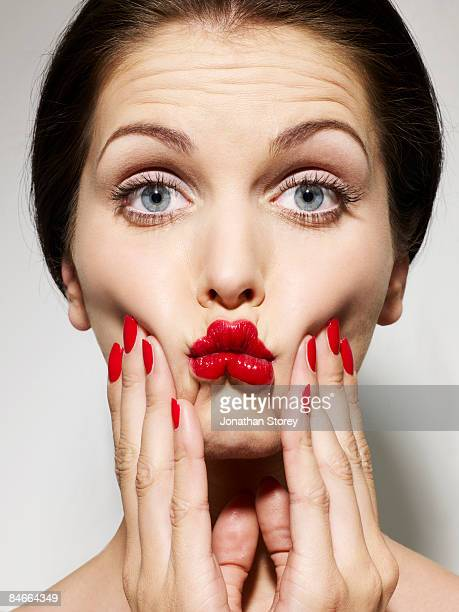 Beauty squeezing cheeks red nails
