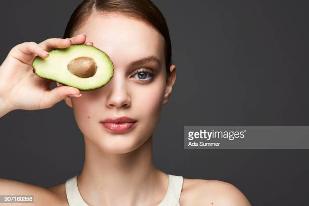 Beauty studio shot of a young girl holding a avocado in front of her eye