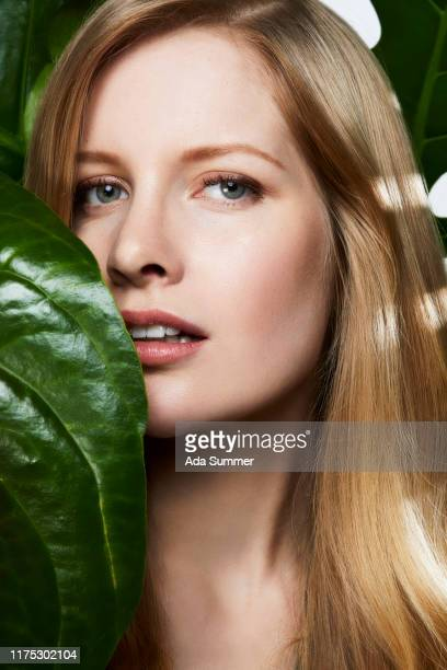 beauty studio  shot of blond haired woman with green leaf - cheveux blonds photos et images de collection