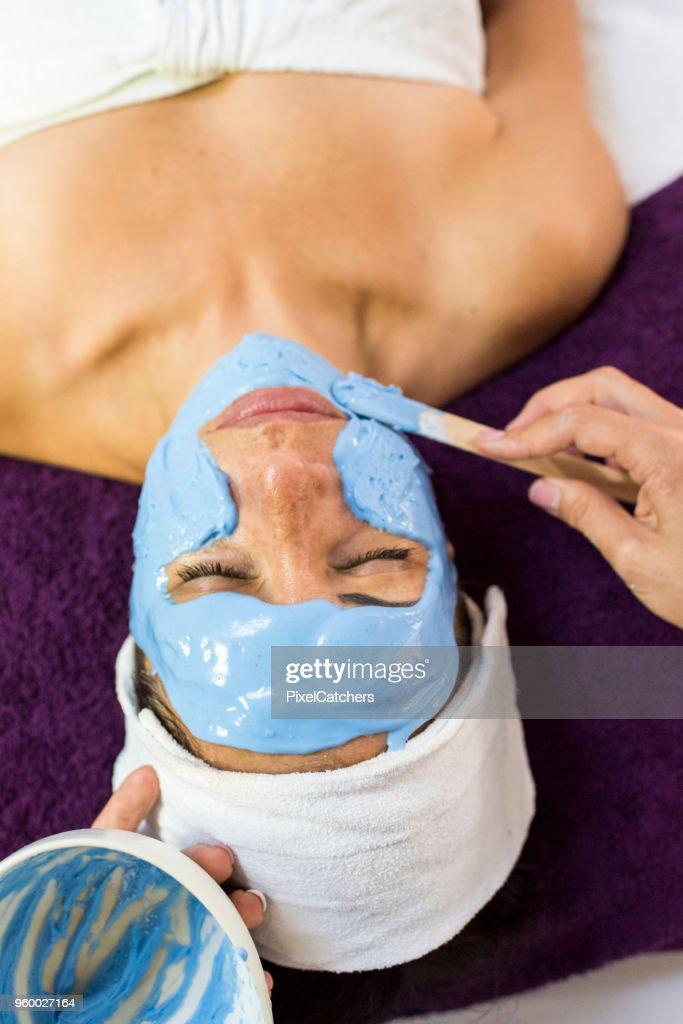 Kosmetikerin, die ein Client eine Gesichtsmaske anwenden : Stock-Foto