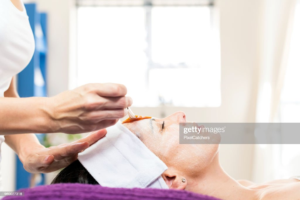 Beauty therapist applying a face mask to a client : Stock Photo