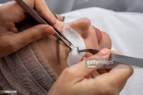 beauty treatment, applying false eyelashes - picking up stock pictures, royalty-free photos & images