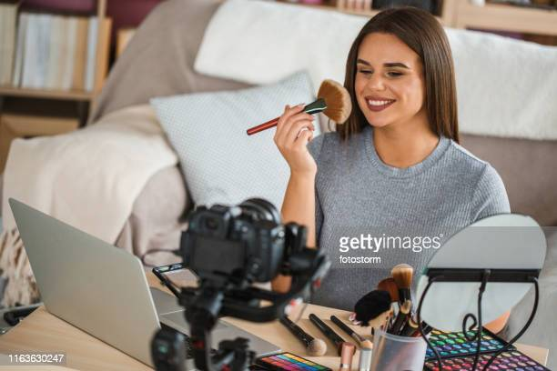 beauty vlogger applying make-up and giving advice to her followers - tutorial stock pictures, royalty-free photos & images