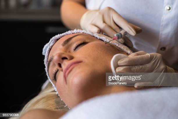 beauty women having botox treatment - botox stock pictures, royalty-free photos & images
