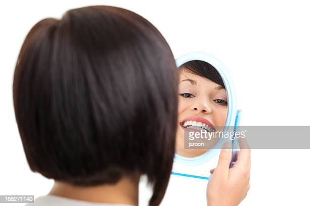 beauty young woman showing her teeth in mirror