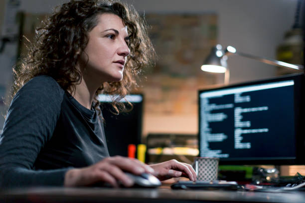 beautyful, concentrated,  female computer hacker stealing information with  computer equipment - fraud job stock pictures, royalty-free photos & images