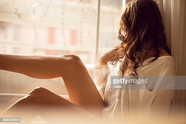beautyful young blond woman sitting next to the balkony door - hot babes stock photos and pictures