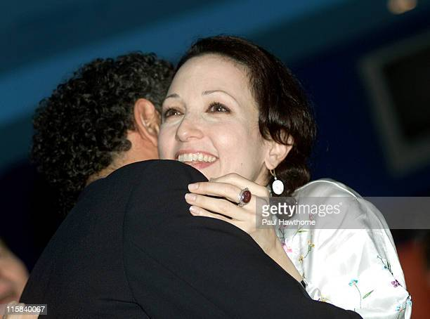 Bebe Neuwirth gets a hug from Brian Stokes Mitchell after watching the PBS event 'Broadway's Lost Treasures' on a video monitor