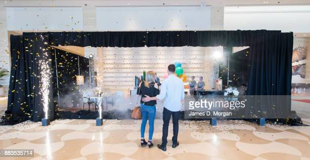 Bec Ormond and Mike Pinker watch as a curtain drops to reveal a live art installation in the hotel lobby of Crown Towers Perth on December 1 2017 in...